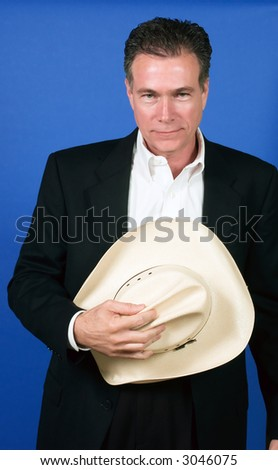 Mature, handsome, white male wearing a black suite and a white shirt holding a cowboy hat with one hand. - stock photo