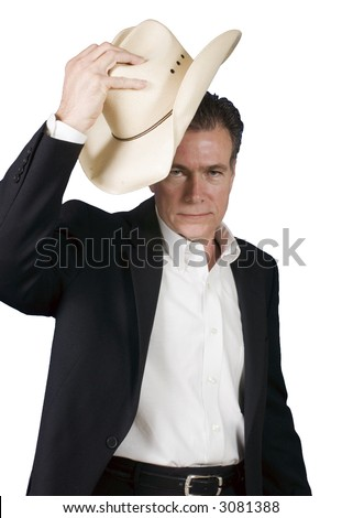 Mature, handsome, white male wearing a black suite and a white shirt holding a cowboy hat with one hand as tipping it in a polite greeting. - stock photo