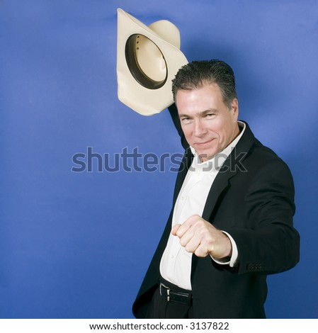 Mature, handsome, white male wearing a black suite and a white shirt holding a cowboy hat with one hand as if in celebration or exhilaration. - stock photo