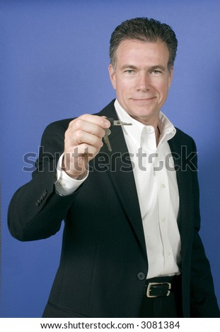 Mature, handsome, white male wearing a black suite and a white shirt holding a set of keys as if offering them to someone. - stock photo