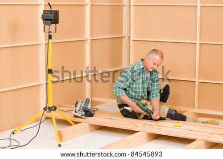 Mature handyman home improvement installing wooden floor in new house