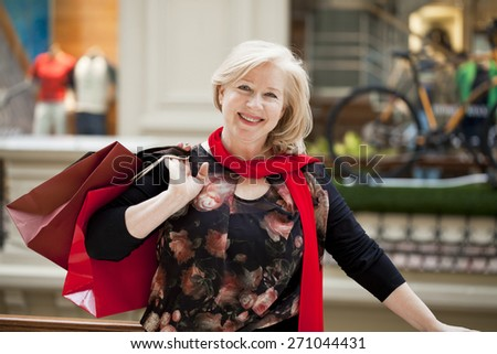 Mature happy blonde woman with shopping bags - stock photo