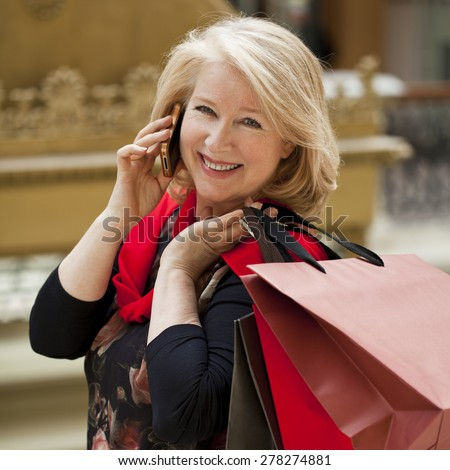 Mature happy blonde woman with shopping bags, calling by phone - stock photo