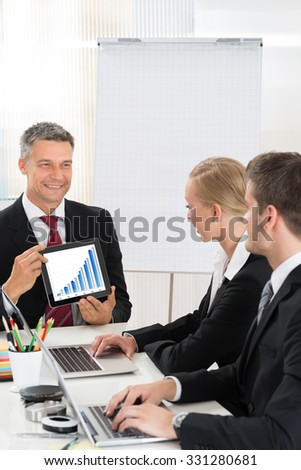Mature Happy Businessman Discussing Graph To Colleagues In Office - stock photo