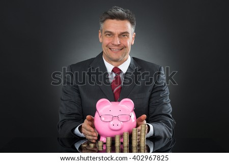 Mature Happy Businessman Sheltering Coins And Piggybank At Desk