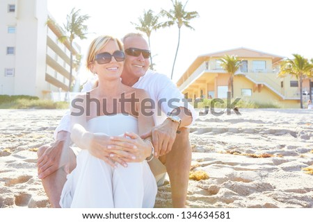 Mature happy couple at the beach sitting down wearing sunglasses. - stock photo