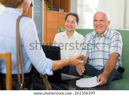 Mature happy couple filling questionnaire for employee with laptop of the bank - stock photo