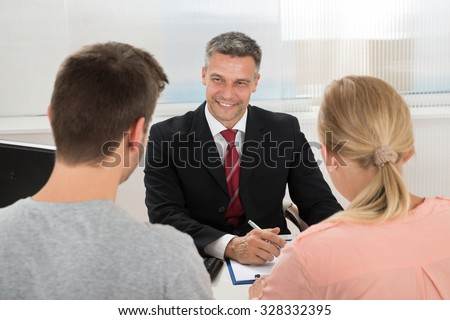 Mature Happy Estate Agent Talking To Young Couple In Office