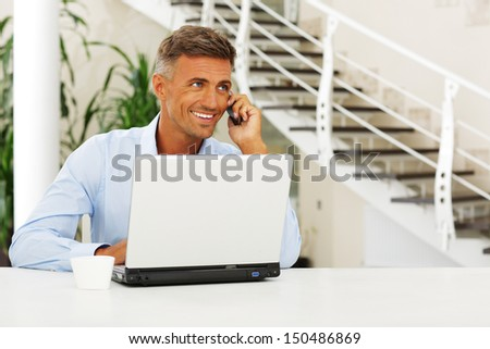 Mature happy man on phone sitting at the desk - stock photo