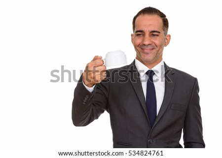Mature happy Persian businessman holding coffee cup upside down
