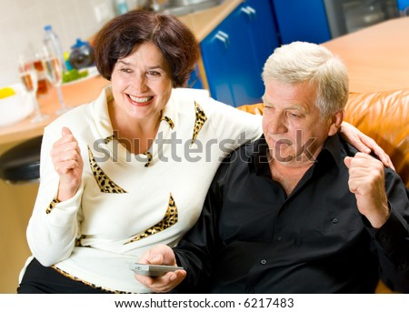 Mature happy smiling couple watching TV together at home - stock photo
