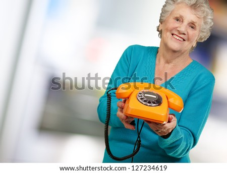 Mature Happy Woman Holding Telephone, Indoor - stock photo