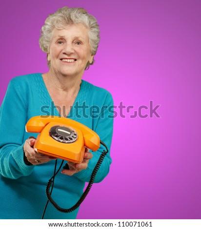 Mature Happy Woman Holding Telephone On Purple Background - stock photo