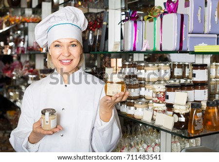 Mature happy woman selling gifts of fine chocolates and confectionery