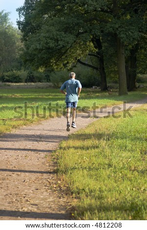 Mature healthy grayhaired man jogging in sunset lights in the park - stock photo