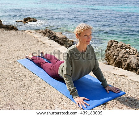 Mature healthy woman in yoga position stretching back by the blue sea, doing yoga and exercising on a sunny holiday, well being, coastal exterior. Senior woman wellness lifestyle, nature outdoors. - stock photo