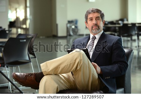 Mature hispanic businessman holding a tablet inside a building