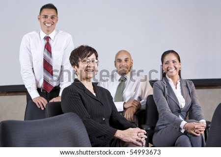 Mature Hispanic businesswoman leading group of younger office workers