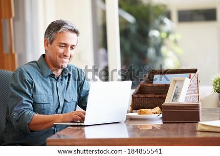 Mature Hispanic Man Using Laptop On Desk At Home - stock photo