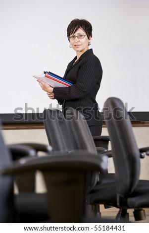 Mature Hispanic professional woman standing with empty chairs - businesswoman or university teacher - stock photo