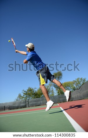 Mature Hispanic tennis player during a match on a sunny day - stock photo