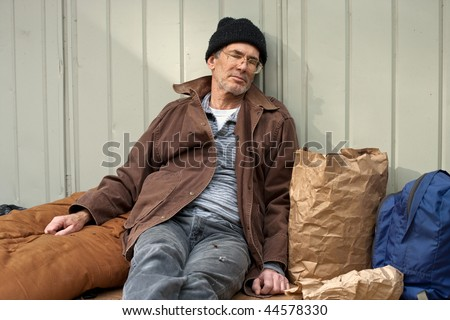 Mature homeless man sleeping in a seated posture, leaning on a metal wall, surrounded by his pack, sleeping bag, etc. - stock photo