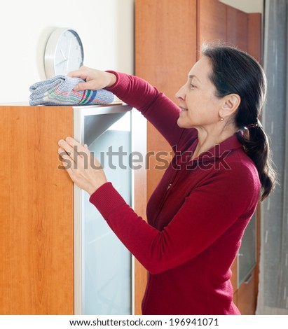 mature housewife dusting glass on furniture with rag and cleanser at home