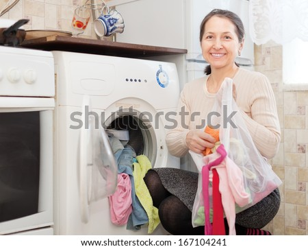 mature housewife loading the washing machine in kitchen