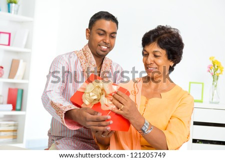 Mature Indian woman receiving a gift from her son - stock photo
