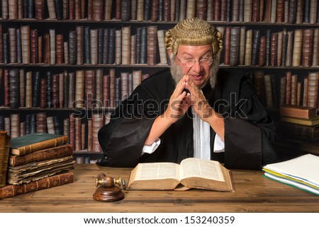 Mature judge in court consulting law books