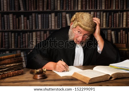 Mature judge with authentic court wig and gavel in court - stock photo