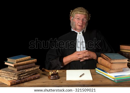 Mature judge with wig and gavel isolated against a black background - stock photo