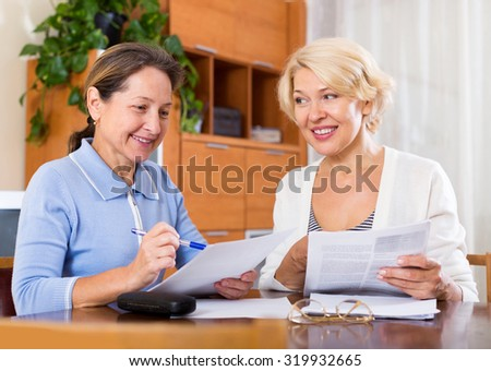 Mature ladies signing documents at office.Focus on the woman on the left - stock photo