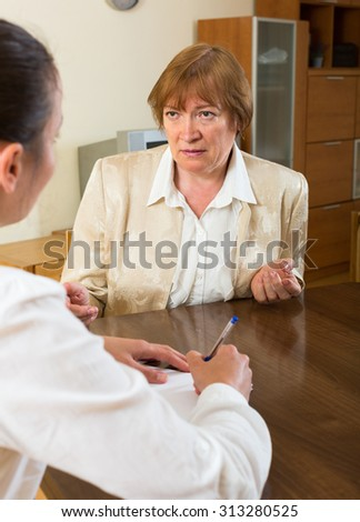 Mature lady and a young woman having a serious meeting in the office  - stock photo