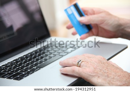 Mature lady at home on line shopping on her laptop and her credit card.