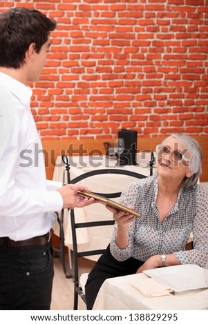 mature lady being served by waiter at restaurant - stock photo
