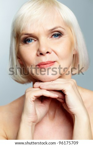 Mature lady looking calmly at camera - stock photo