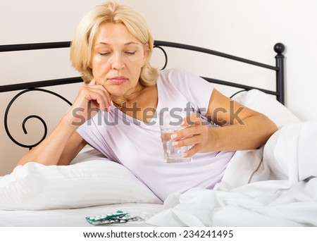 mature lady with pills and vitamins in bed - stock photo