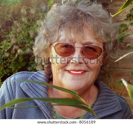 Mature lady working in the garden enjoying her leisure - stock photo