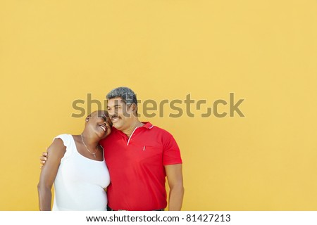 mature latin american couple hugging and smiling with yellow wall in background. Waist up, copy space - stock photo