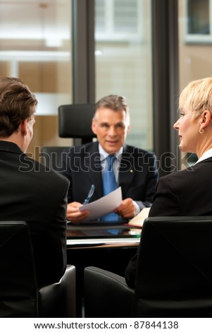 Mature lawyer or notary with clients in his office in a meeting - stock photo