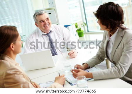 Mature leader approving fresh ideas of his colleagues - stock photo