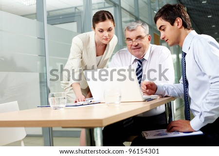 Mature leader using laptop while his younger employees looking at the screen - stock photo