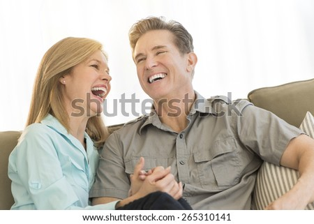 Mature loving couple laughing while holding hands on sofa at home - stock photo