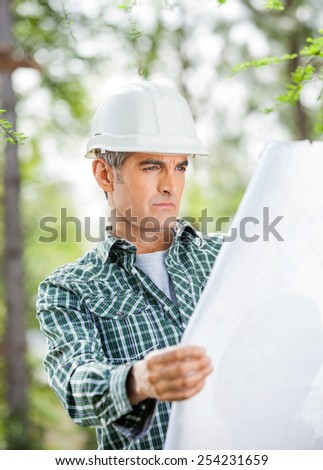 Mature male architect analyzing blueprint at construction site - stock photo