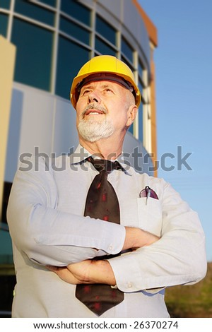 Mature male architect looking up at construction site