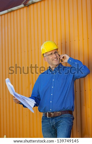 Mature male architect using mobile phone against trailer - stock photo