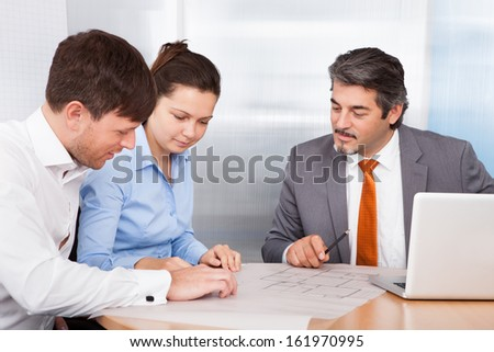 Mature Male Broker Explaining Plan To Young Couple - stock photo