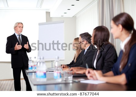 Mature male business executive training his associates during a meeting at office - stock photo
