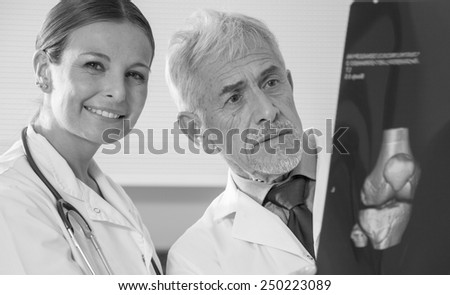 Mature male doctor and young female assistant analyzing patient x-ray test. - stock photo
